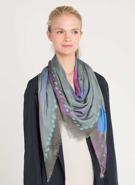Limited edition scarf in subtle hues of muted grey-greens, mauves and slate blues in varying sizes of dots and circles on a soft light fabric. The model with the scarf draped around the neck over a navy trench. Alba Amicorum's Ascending space.