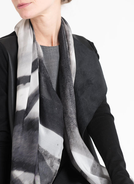 Close crop of the model shows a monochromatic styling with Alba Amicorum's limited edition scarf in airy silk chiffon. The black and white and grey shades translate ink and brush work inspired by bare trees named, Autumn's Rendition 1.
