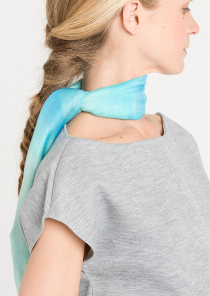 Tight crop of the model's profile shows Alba Amicorum's limited edition scarf tied in an elegant knot around the neck. Before the Road, as the scarf is named, is  ultra soft and is styled with a cool gray t-shirt.