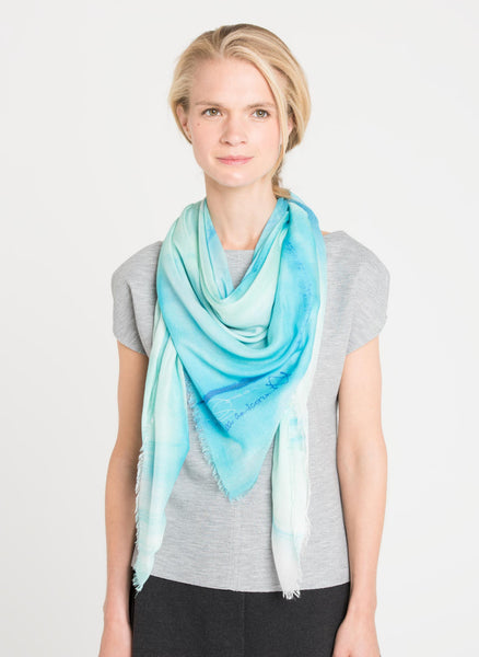 Front view of the model shows Alba Amicorum's limited edition scarf is loosely draped around the neck. Before the Road, as the scarf is named, is ultra soft and is styled with a cool gray t-shirt.