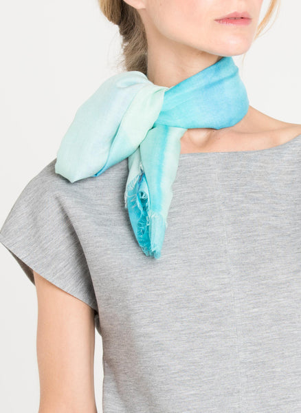 Close up of the model has Alba Amicorum's ultra soft scarf folded in quarters and tied like a chocker in a simple knot. Styled with cool grey t-shirt, Before the Road, as the scarf is named, is in shades of aqua blues in fluid water colours.
