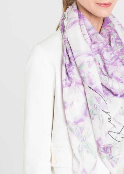 A closeup three quarters view of the model shows Alba Amicorum's limited edition scarf, Beguiling Trajectory, draped around the neck over a white blazer. The kaleidoscopic arrangement of Lillies form an intricate lilac and green dial.