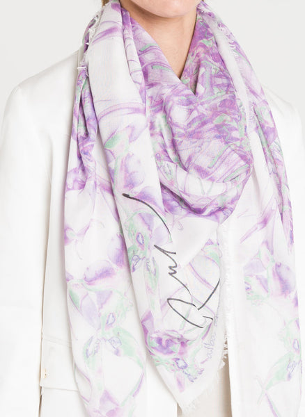 A closeup three quarters view of the model shows Alba Amicorum's limited edition scarf with the artist's signature. Beguiling Trajectory is draped around the neck over a white blazer. The kaleidoscopic arrangement of Lillies form an intricate lilac and green dial.