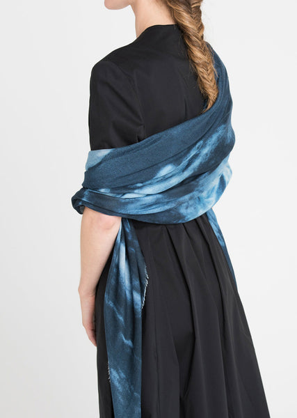 Back of the model wearing a  navy dress with batik like blues scarf. Limited edition scarf by Alba Amicorum named beyond the atmosphere is a photograph of the blue sky taken through a prism which created angel like abstract forms.
