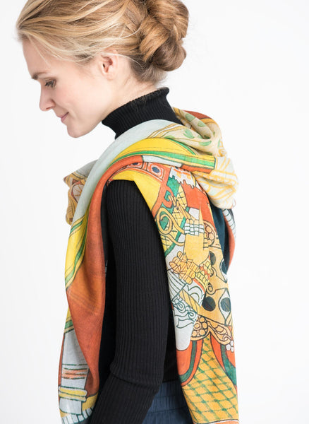 Side view of model draped in Alba Amicorum's Dasha-Hara scarf. Limited edition cashmere scarf details beautiful drawings of two elaborately decorated horses with their riders composed as a mirror image. Rich warm colours, original painted in gauche.