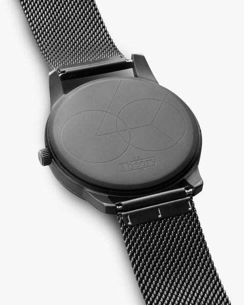 Matte all black mesh watch facing down showing the detailed design of the back of the watch. Our Theory Of.