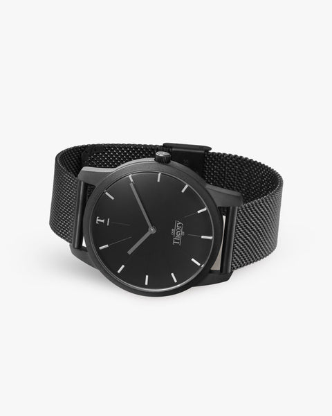 Matte all black mesh watch lying down on the side.