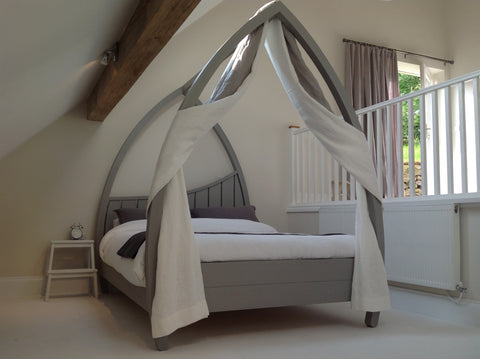 Grey four poster bed made from solid hardwood.