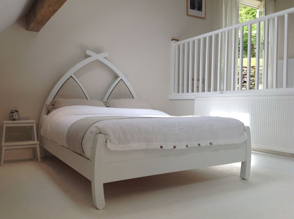 Modern white wooden bed with upholstered arched headboard