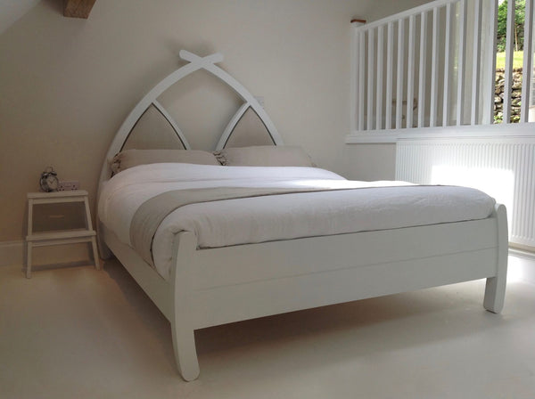 Handmade wooden bed with linen headboard