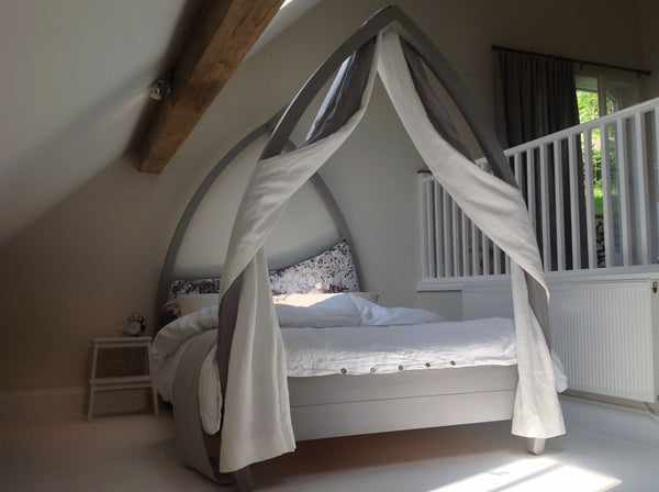 Grey four poster bed with drapes and bent posts