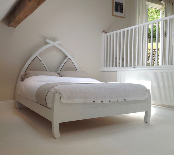 White wooden bed with upholstered headboard