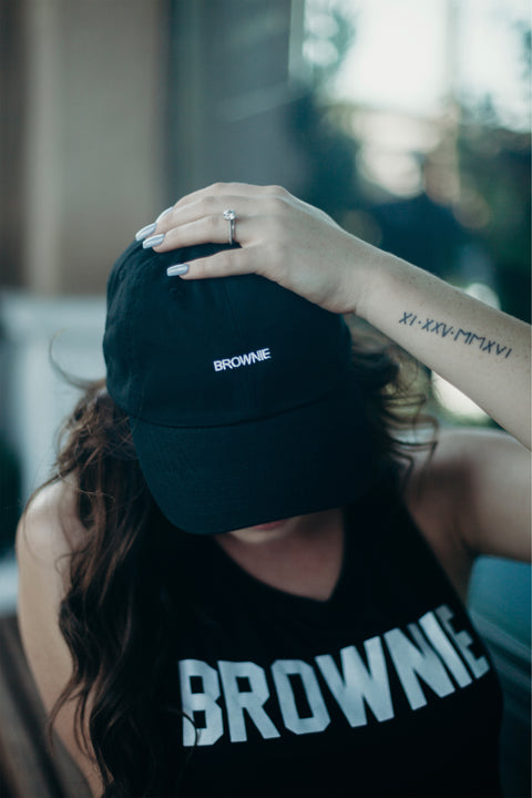 lifestyle photo of a brunette wearing our dad hat and tank top