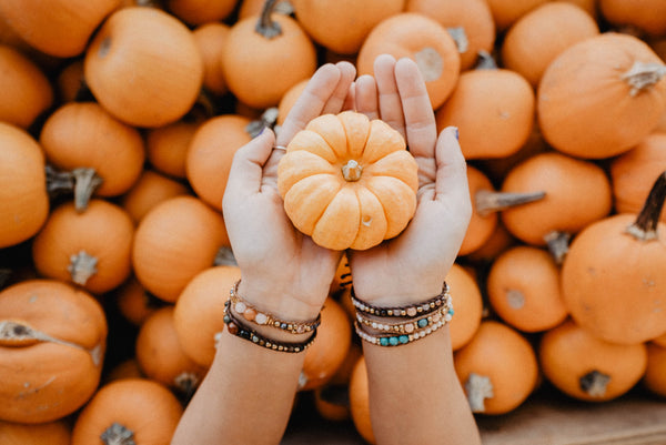 holding pumpkin with bracelets