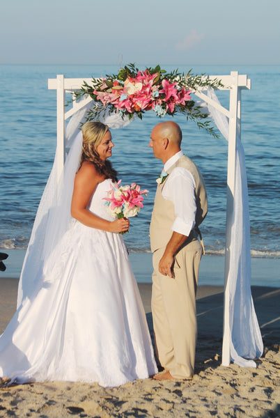little miss lovely floral design // white vinyl archway beach wedding