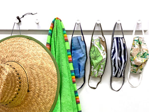Large straw hat hanging next to a bright green beach towel with matching multi colored stripes at the edges and four face masks.