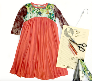 Image shows a colorful children's dress next to one of our custom design papers, scissors, three colored pencils and scraps of fabric that match the dress. The base of the dress is salmon with a green floral bust and brown tie dye arms.