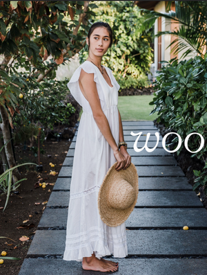 Clickable image of a woman wearing a lowly white dress, holding a straw hat, bare foot in a tropical setting.