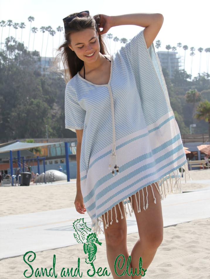 Clickable image of a woman wearing a blue poncho with white stripes at the bottom at the beach.
