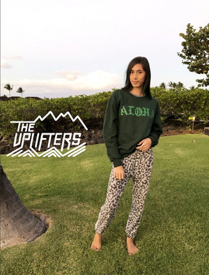 Clickable image of a woman wearing a Aloha pull over sweatshirt, leopard sweatpants and bare foot on a grassy lawn.