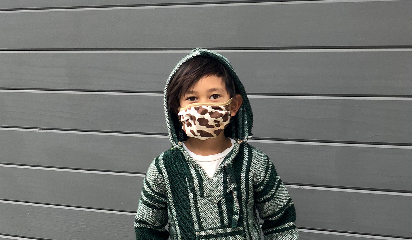 A cropped image of a boy in a leopard face mask, hoodie and white tee shirt against a grey wall.