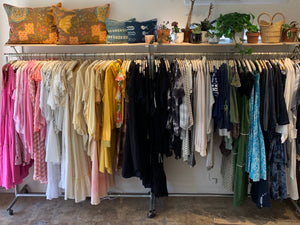 Image shows two full clothing racks and a shelf at the top of both. From left to right the clothing rack shows pink, white, orange, black, grey and navy clothing. The two shelves are full of plants, books, baskets and 4 throw pillows.