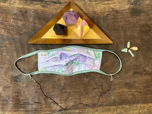 Face mask with purple iridescent chain. Golden triangle tray filled with crystals.