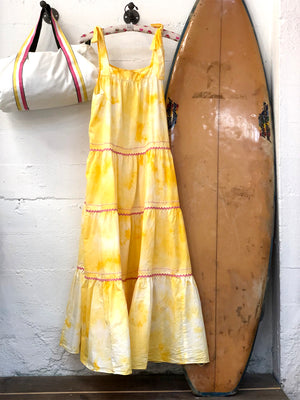 Maxi dress with tie shoulder straps in white and yellow tie dye aka sunshine wash hanging next to a surf board and small white duffle bag. Pink ric ran trim along each tier of the dress.