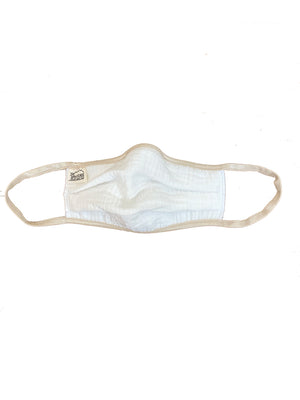 White gauze mask with beige elastic against white background