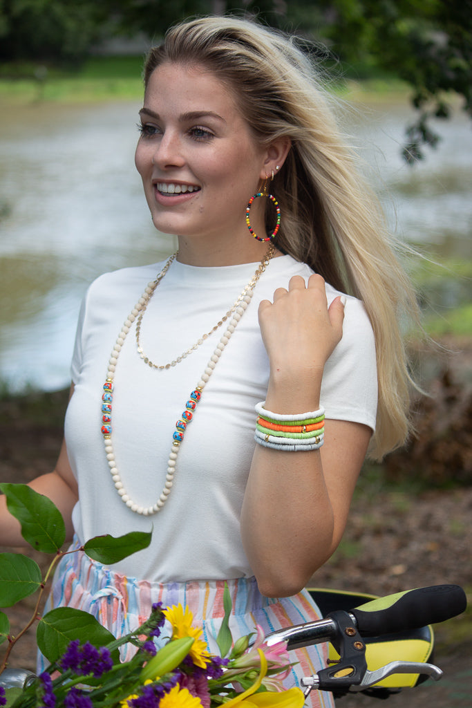 A girl with a white shirt and bracelets