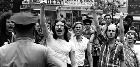 Image of the STONEWALL RIOTS, 1969. Men holding hands up and shouting fed up with laws established then