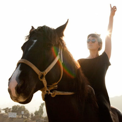 Cate Le Bon riding a horse with her arm up in the air