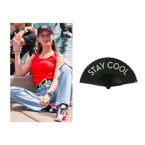 Bella Hadid at Grand Prix wearing relaxed jeans, sneakers and vest top. Khu Khu Stay Cool fan in image
