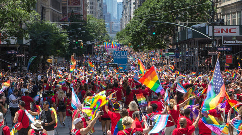 NEW YORK PRIDE. View up the main street with HUGE CROWDS and SEVERAL RAINBOW FLAGS