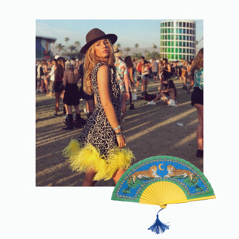 photo of instagrammer Sukilov at Coachella 2019  wearing leopard dress with yellow frill and Khu Khu lazy leopard hand fan