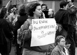 Woman holding up sign Discrimination is ALWAYS WRONG at one of the original LGBT marches