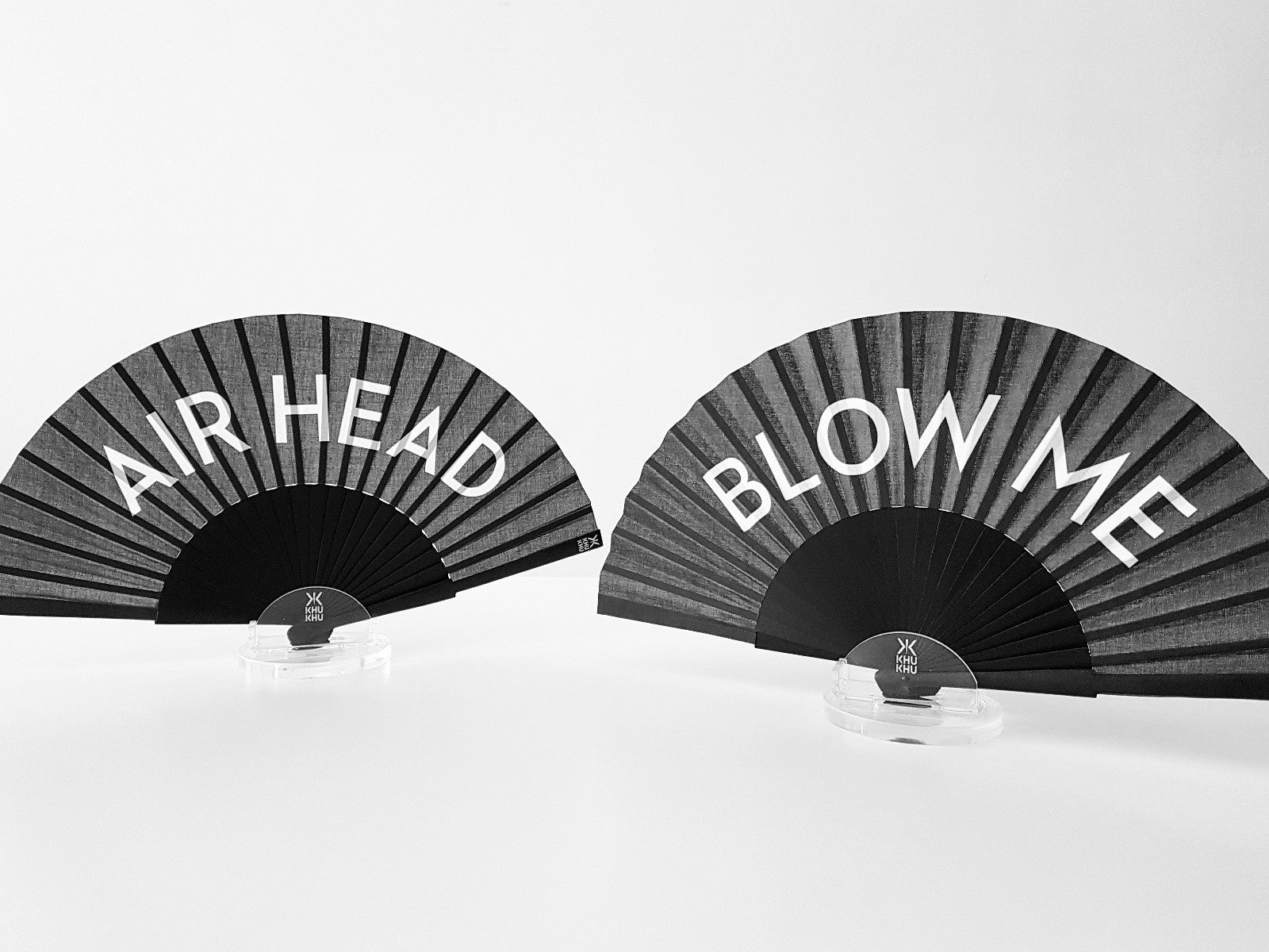 Khu Khu Blow Me and Airhead Statement hand-fans in acrylic stands on a table.
