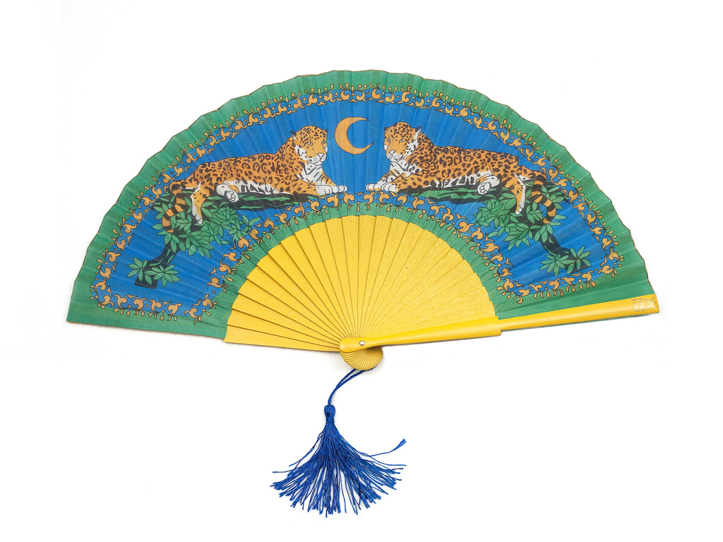 Khu Khu Lazy Leopards Cool Cats Hand-Fan. Two leopards sit in branches with blue night sky in background mounted with painted yellow sticks with loop and blue tassel.