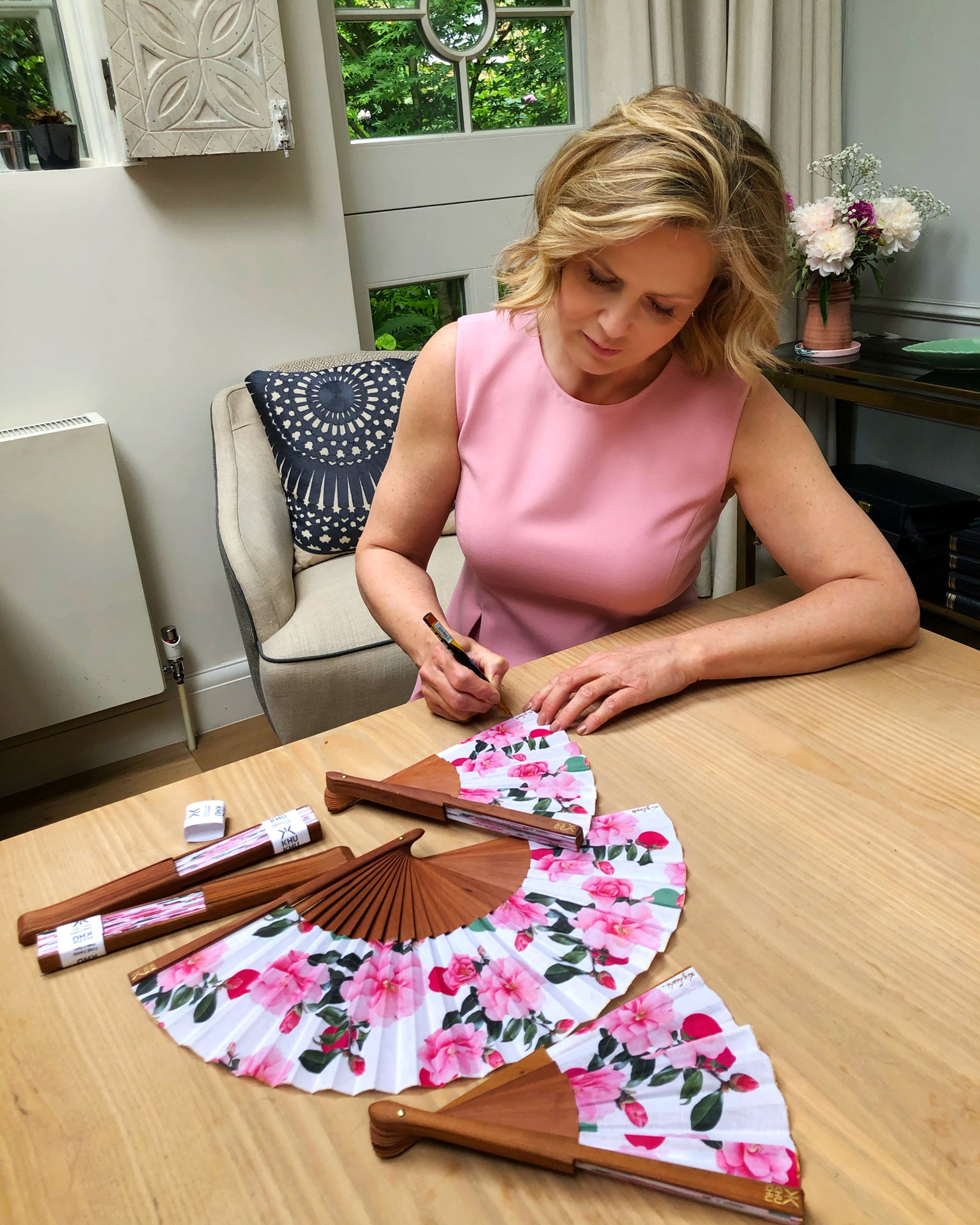 Liz Earle signing  Khu Khu Beautiful Cool Camellias Hand-Fan with collaboration print (Floral with pink and green spots and camellias.)
