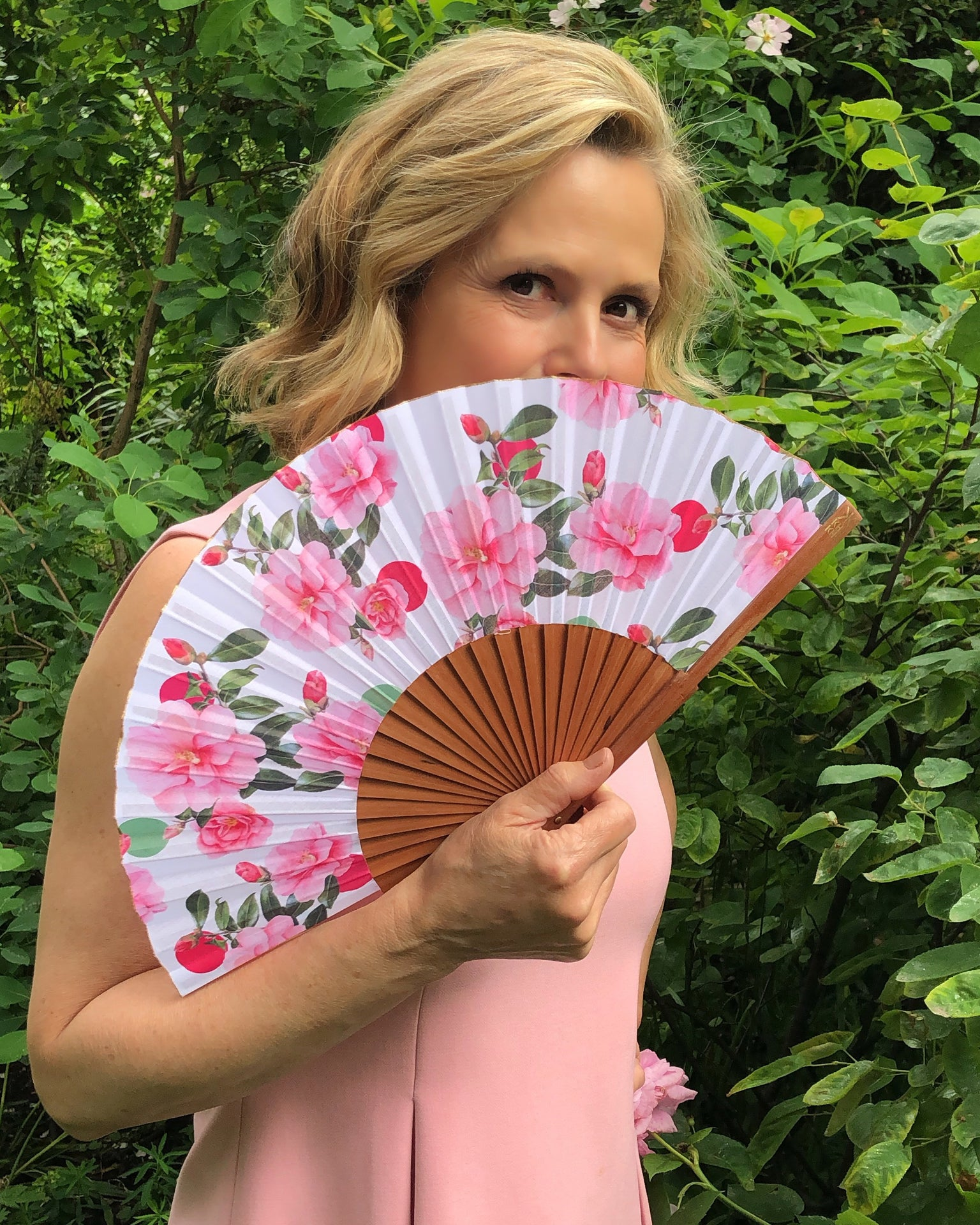 Liz Earle holding Khu Khu X Liz Earle Beautiful Cool Camellias Hand-Fan with collaboration print (Floral with pink and green spots and camellias.)