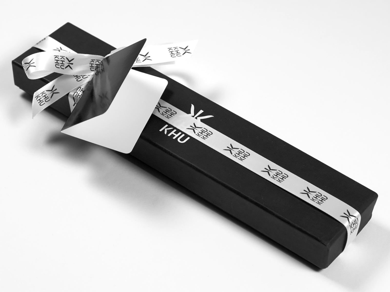 Khu Khu luxury gift wrap. Fan is placed in cotton bag then wrapped in tissue and then put in box, wrapped in ribbon and given a black glossy tag.