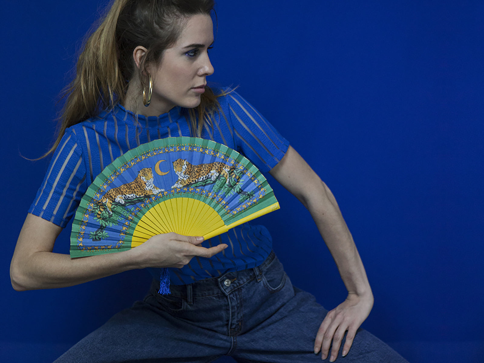 Model wearing blue on background using Khu Khu Lazy Leopards Cool Cats Hand-Fan. Two leopards sit in branches with blue night sky in background mounted with painted yellow sticks with loop and blue tassel.