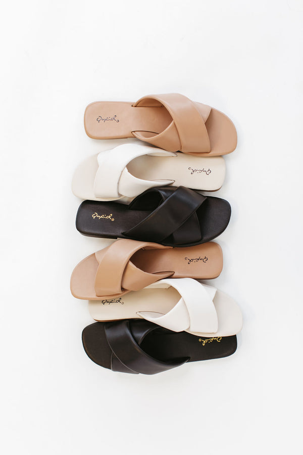 Slides are slip on sandals with a large criss cross pattern across the arch available in three colors.