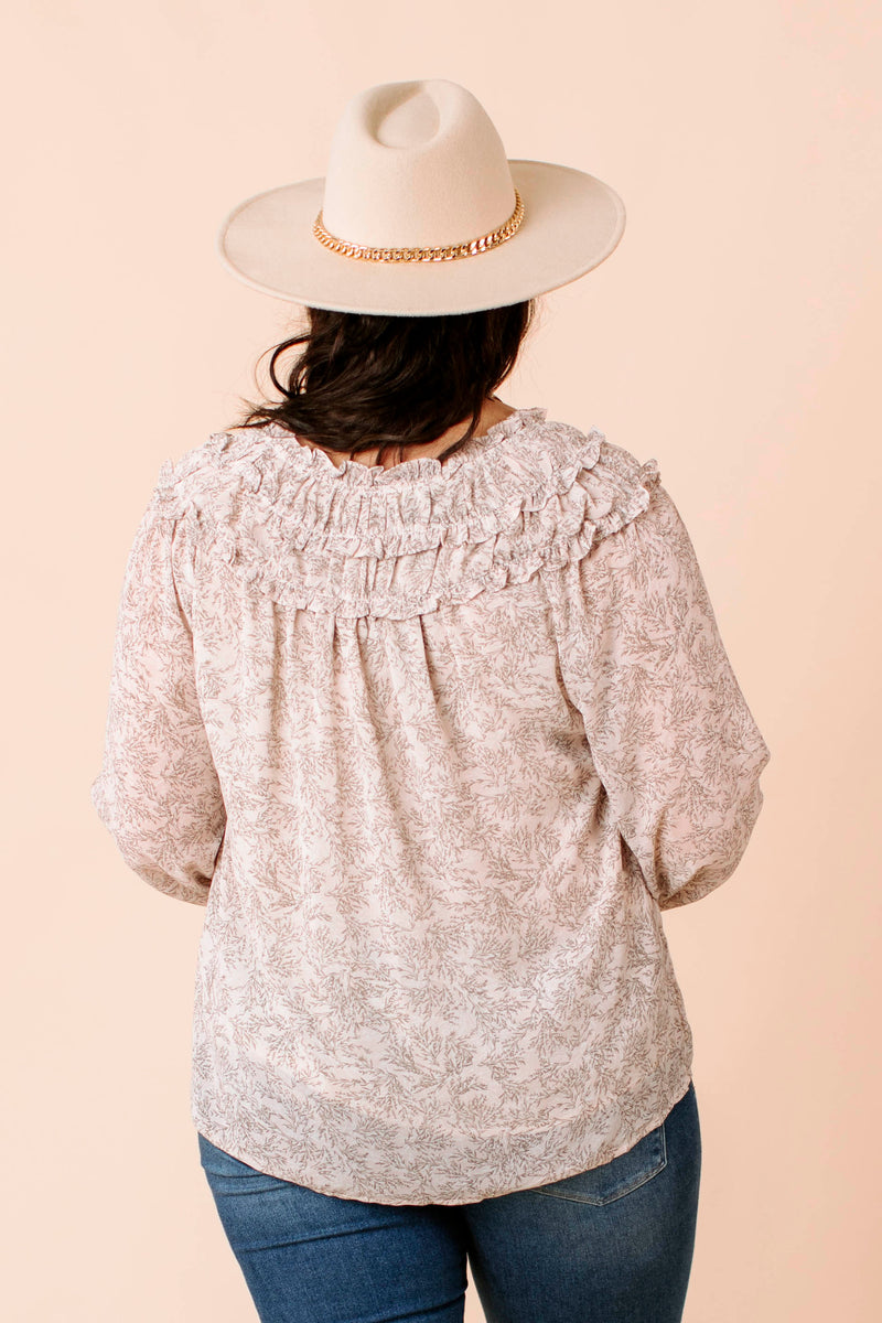 solid babydoll top that has a mock neckline, and raglan bijoux sleeve as well as ruffle hem.