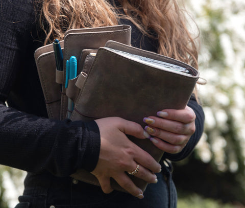 Gray leather travelers notebook covers. Person holding journal covers.