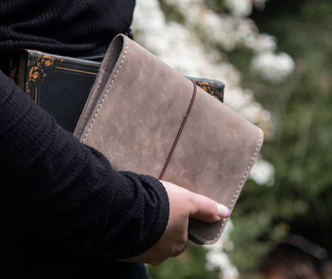 Tan leather notebook cover. Person holding leather journal cover.