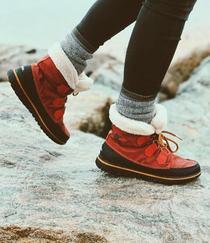 person wearing boots on rocks