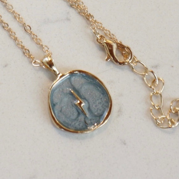 Collier en or éclair sur fond bleu ciel / Gold Necklace with Lightning on Sky Blue Background