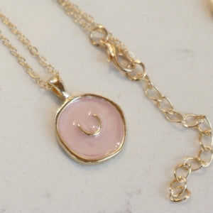 "Collier en or ""U"" sur fond rose / Gold Necklace with ""U"" on Pink Background"