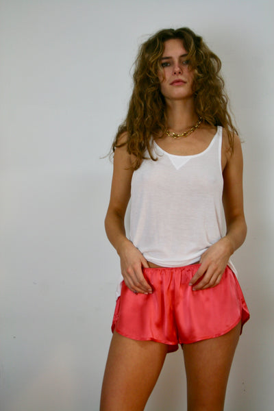Coral silk athletic shorts with a curved slit on the side add a bit of punch to your routine! shown with our ribbed tank top.  Charlie is wearing an extra white ribbed tank top small for a youthful fit. model has big curly blonde hair and is wearing a gold liked chain with her outfit.